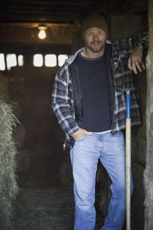 pacific islander ethnicity: Man smiling in barn doorway with pitchfork