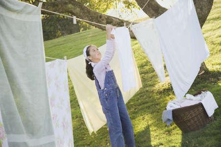 islander: Pacific Islander girl hanging laundry on clothesline