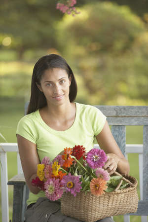 african basket: African woman sitting with basket of flowers
