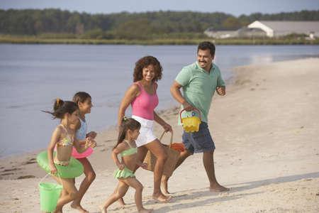 vacationing: Hispanic family running on beach