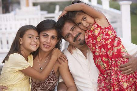hispanic ethnicity: Hispanic family hugging on porch