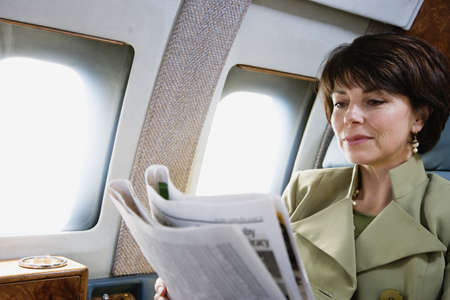 transporting: Businesswoman reading newspaper on private airplane