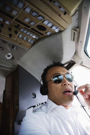 seriousness skill: Asian male pilot in cockpit of airplane