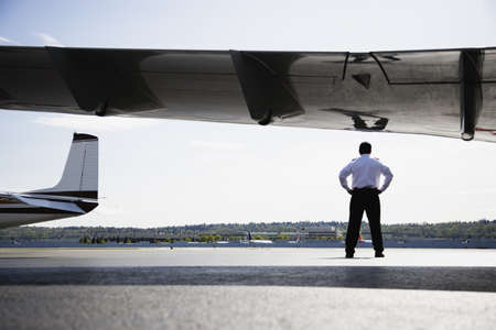 pacific islander ethnicity: Rear view of pilot standing next to airplane wing on tarmac LANG_EVOIMAGES
