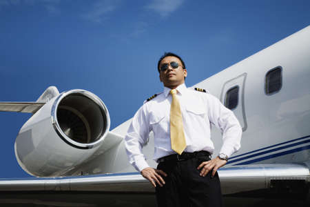 stepping: Asian male pilot standing near airplane LANG_EVOIMAGES