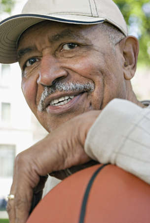 longshot: Close up of senior African man smiling with basketball