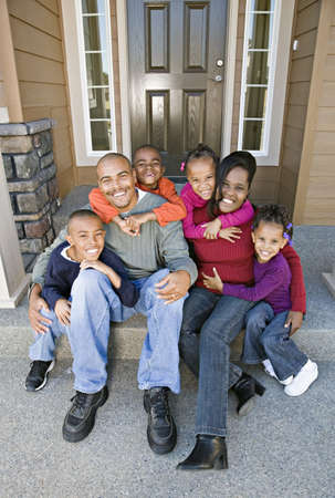 front view: African family sitting on front steps