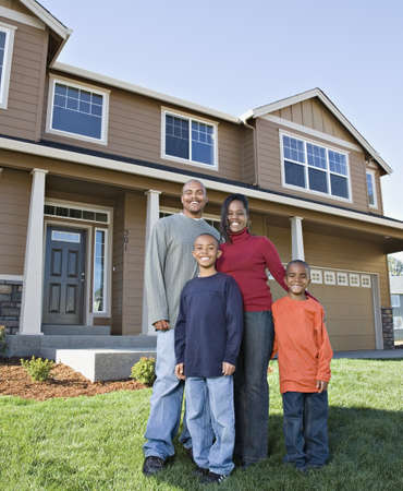 black couple: African family posing in front of house