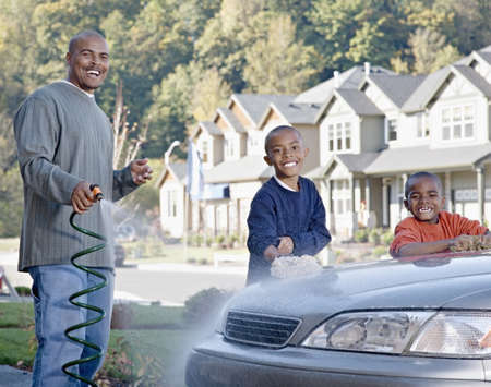 fathering: African father and sons washing car in driveway
