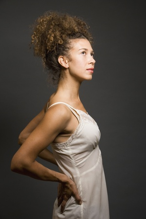 underskirt: Studio shot of Hispanic woman wearing slip with hands on back LANG_EVOIMAGES