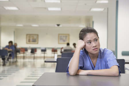 concentrates: Asian female doctor sitting at table leaning head on hand