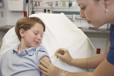 Young boy receiving injection from nurse