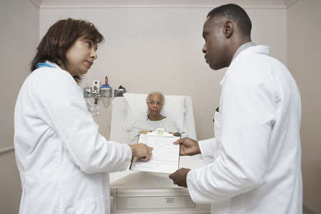 African male and female doctors discussing senior patient's chart