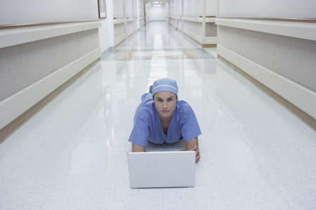 Female doctor laying in corridor using laptop