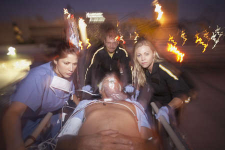 Doctors wheeling emergency patient on gurney outdoors at night