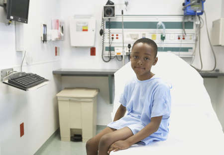 attentiveness: African boy sitting on edge of hospital bed