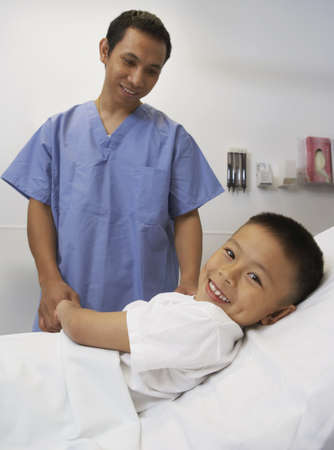 scrub cap: Asian boy smiling with male nurse in hospital