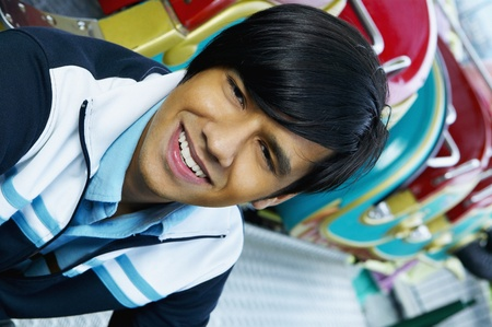 Close up of young Hispanic man smiling next to carnival ride Stock Photo