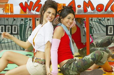 Two young Hispanic women sitting on carnival booth Stock Photo