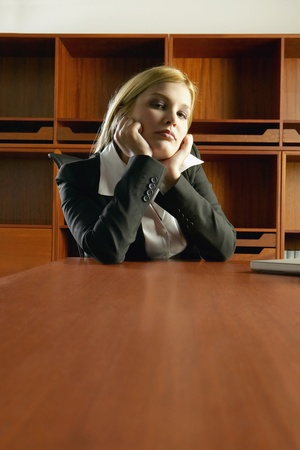 Young Hispanic businesswoman sitting at conference table leaning chin in hands