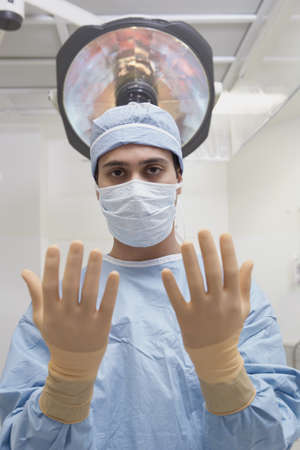 three persons only: Indian male surgeon holding up gloved hands in operating room LANG_EVOIMAGES