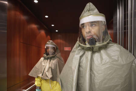 seriousness skill: African man and woman in hazmat suits LANG_EVOIMAGES
