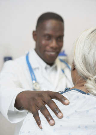 African male doctor reassuring senior patient Stock Photo