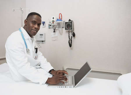 ninetys: African male doctor using laptop on hospital bed LANG_EVOIMAGES