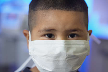 three persons only: Close up of young Asian boy wearing surgical mask