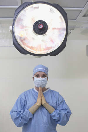 hindering: Female surgeon praying in operating room LANG_EVOIMAGES