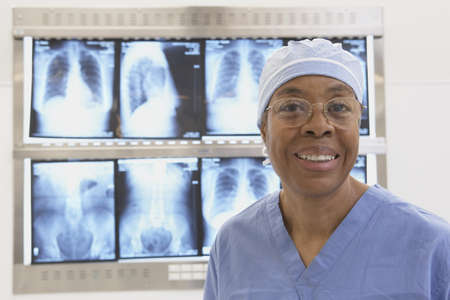 Senior African female doctor smiling in front of x-rays on lightbox