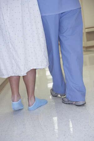scrub cap: Rear view of nurse and patient walking in corridor