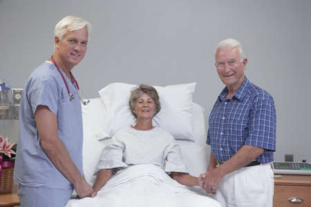hindering: Senior female patient and husband smiling with doctor in hospital room