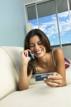 wearying: Hispanic woman laying on sofa using cell phone with credit card