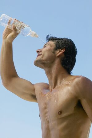 barechested: Bare-chested Asian man pouring water over head LANG_EVOIMAGES