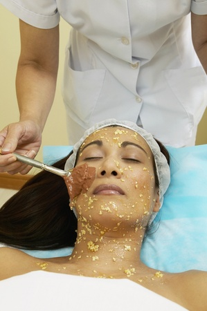 wearying: Asian woman receiving facial spa treatment LANG_EVOIMAGES