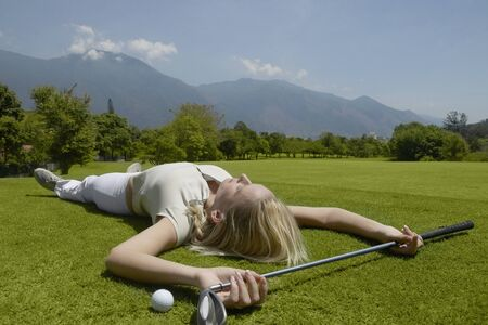 Woman laying on golf course with golf club and golf ball Stock Photo