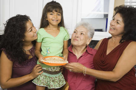 gramma: Multi-generational Hispanic female family members smiling in kitchen