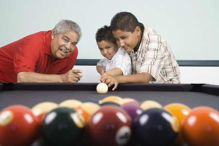 gramma: Hispanic grandfather teaching grandsons to play pool