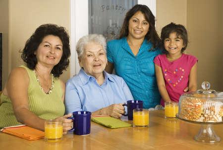 gramma: Multi-generational Hispanic female family members smiling at breakfast table LANG_EVOIMAGES