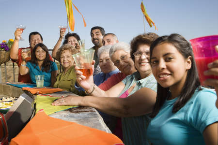 Large Hispanic family toasting at party outdoors LANG_EVOIMAGES