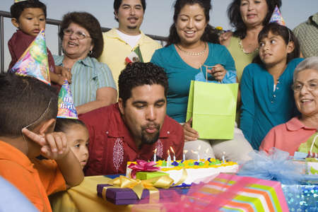 latin couple: Hispanic man blowing out candles on birthday cake with family LANG_EVOIMAGES