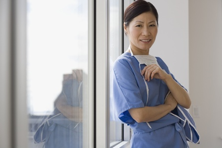 Aziatische vrouwelijke arts leunend tegen raam lachend