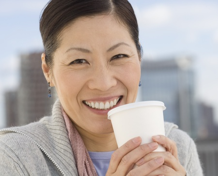 gramma: Middle-aged Asian woman holding coffee cup outdoors