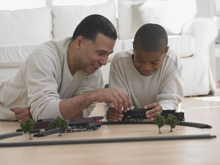 African father and son playing with model train on floor 스톡 콘텐츠