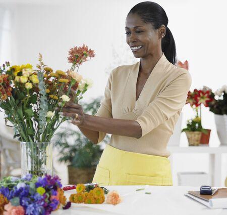 scrub cap: African female florist arranging flowers in shop