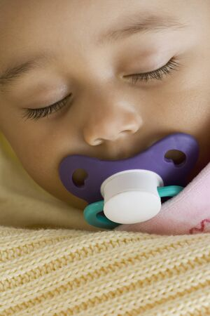 bedcover: Close up of Hispanic baby sleeping with pacifier LANG_EVOIMAGES