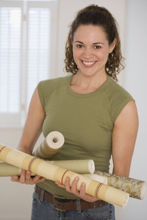 seriousness skill: Hispanic woman holding rolls of wall paper