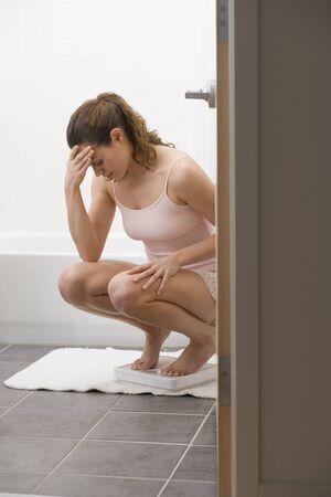 Hispanic woman frowning on bathroom scale