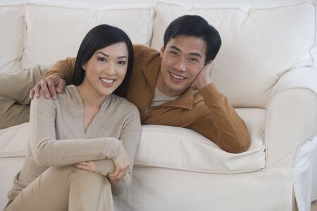 seriousness skill: Asian couple smiling on sofa